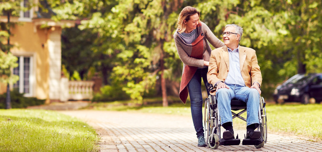 senior man in a wheelchair and his caregiver