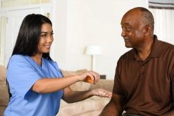 caregiver helping an senior patient take his medication