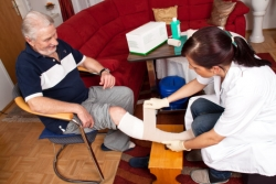 caregiver taking care of an senior man's wound